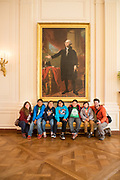 Students from Kemper Elementary, in Cortez, Colorado wait to visit the White House Kitchen Garden under a portrait of George Washington in the White House.