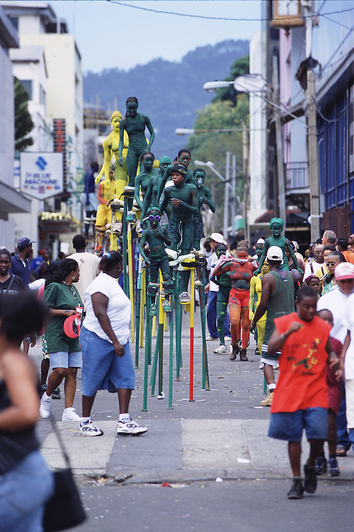 "Trinidad and Tobago ""MOKO JUMBIES: The Dancing Spirits of Trinidad"".(The jounger Moko Jumbies, protected by their older peers and handlers, always take the lead.  Handlers are an important part of a Moko Jumbie parade, they are friends, relatives and students who are in charge of the Moko Jumbies safety and needs like drinks and snacks. They also ""catch"" a stilt walker, when they need to come down to fix their stilts or push them back up when ready to walk again).A photo essay about a stilt walking school in Cocorite, Trinidad..Dragon Glen de Souza founded the Keylemanjahro School of Art & Culture in 1986. The main purpose of the school is to keep children off the streets and away from drugs..He first taught dances like the Calypso, African dance and the jig with his former partner Cathy Ann Samuel.  Searching for other activities to engage the children in, he rediscovered the art of stilt-walking, a tradition known in West Africa as the Moko Jumbies , protectors of the villages and participants in religious ceremonies. The art was brought to Trinidad by the slave trade and soon forgotten..Today Dragon's school has over 100 members from age 4 and up..His 2 year old son Mutawakkil is probably the youngest Moko Jumbie ever. The stilts are made by Dragon and his students and can be as high as 12-15 feet. The children show their artistic talents mostly at the annual Carnival, which today is unthinkable without the presence of the Moko Jumbies. A band can have up to 80 children on stilts and they have won many of the prestigious prizes and trophies that are awarded by the National Carnival Commission. Designers like  Peter Minshall , Brian Mac Farlane and Laura Anderson Barbata create dazzling costumes for the school which are admired by thousands of  spectators. Besides stilt-walking the children learn the limbo dance, drumming, fire blowing and how to ride  unicycles..The school is situated in Cocorite, a suburb of Port of Spain, the capital of Trinidad and Tobago..all"