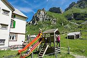 Childrens playground. Berggasthaus Meglisalp can only be reached on foot in the spectacular heart of the Alpstein mountain chain in the Appenzell Alps, Switzerland, Europe. This authentic mountain hostelry, owned by the same family for five generations, dates from 1897. Meglisalp is a working dairy farm, restaurant and guest house surrounded by majestic peaks above green pastures.