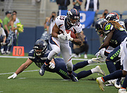 Aug 8, 2019; Seattle, WA, USA; Denver Broncos running back Devontae Booker (23) is defended by Seattle Seahawks defensive back Shalom Luani (24)  in the first quarter at CenturyLink Field. The Seahawks defeated the Broncos 22-14.
