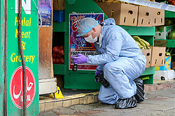 © Licensed to London News Pictures. 13/10/2019. London, UK. A forensic officer gathers evidence at the entrance of  West Green Halal Meat and Groceries store on West Green Road in Tottenham, North London where two men were stabbed and rushed to hospital shortly after 9.30am this morning. The ages of the two victim and their condition is not yet know. Photo credit: Dinendra Haria/LNP