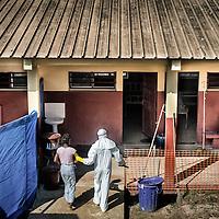 21/11/2014. Nzerekore. Guinee Conakry.<br /> <br /> <br /> De dos, Cecile Loua , 16 ans, &eacute;tudiante.<br /> Elle a &eacute;t&eacute; en contact avec Mamy Messa son mari qui est sorti apr&egrave;s avoir &eacute;t&eacute; confirm&eacute; Ebola.<br /> <br /> Assises en face.<br /> Matenin Fofana (&agrave; gauche), 60 ans, m&eacute;nag&egrave;re, entre dans le centre de transit.<br /> <br /> Veuve, son mari Manadi Somaoro est d&eacute;c&eacute;d&eacute; suite a infection par le virus Ebola.<br /> <br /> &Agrave; droite: <br /> <br /> Soumaoro Man&eacute;ma (avec bebe), 38 ans, m&eacute;nag&egrave;re.<br /> En contact avec son p&egrave;re Manadi Somaoro, deced&eacute; Ebola confirm&eacute;.<br /> <br /> Sylvain Cherkaoui/Cosmos pour Alima