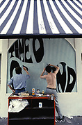 Two men painting letters on to a window of a shop, UK 1970's