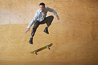 Young Businessman Performing Skate Trick in Half-Pipe