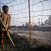 Agra, November 2003. A disabled boy watches the merriment of other children on the sandy bank of the Yamuna river opposite the Taj Mahal, the most recognized symbol of India worldwide.