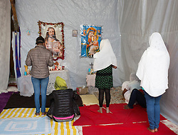 © Licensed to London News Pictures. 30/08/2015. Calais, France. Christian women pray at the Sunday mass in the Ethiopian Orthodox church in the centre of the refugee camp in Calais, also known as the Jungle. Tomorrow the French PM, Manuel Valls, will visit the day centre Jules Ferry at the camp. Photo credit : Isabel Infantes/LNP