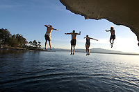 Four people are in mid-air jumping from the Malaspina Galleries cliffs on Gabriola Island, BC at sunset.