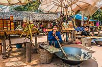 Angkor, Cambodia - January 2, 2014: girl making and selling sugar cane sweets at Angkor Cambodia on january 2nd, 2014