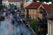 Crowds are moving across Charles Bridge - in between a cleaning car from then city of Prague -seen from the Lesser Town (Mala Strana) Bridge Towers towards the city center.