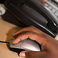 Close-up of an African-American's hands on a computer mouse with a telephone in the background