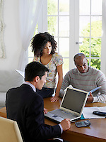Couple sitting at dining table with financial advisor