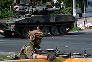 A US soldier with an M60 machine gun and backed by a tank takes position to secure a neighborhood from Panamanian army troops during the US invasion of Panama, December 1989.