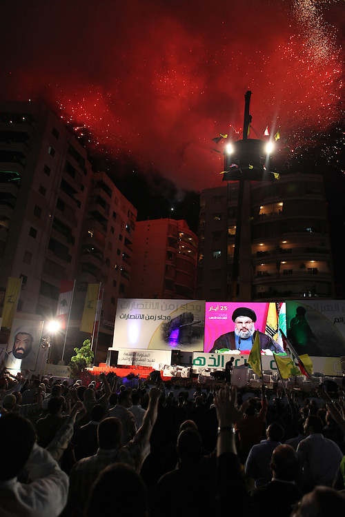 Supporters of the Shiite resistance and political group, Hizballah, rallied in the Dahiyeh southern suburbs of Beirut to watch a televised speech from Hizballah General Secretary Hassan Nasrallah. The rally was called for by Hizballah to celebrate Land Day, which is the 9th anniversary of Israel's withdrawal from southern Lebanon, which Hizballah and its supporters say was a victory over Israel. The rally comes just 13 days before Lebanese go to the polls to elect a new parliament. With Sunni Muslims and Shia Muslims mostly supporting their respective sectarian parties, Nasrallah praised Christian leader Michel Aoun. Aoun is head of the Free Patriotic Movement, which is allied with the Hizballah-led opposition March 8 coalition. ///Hizballah supporters cheer as Hassan Nasrallah appears on screen to deliver his televised speech as fireworks go off from the surrounding buildings.