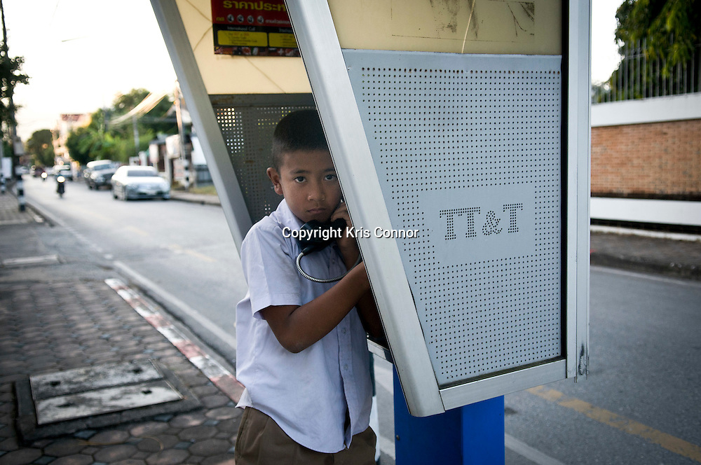 A school boy talks on a public telephone in Chiang Mai, Thailand. Photo by Kris Connor