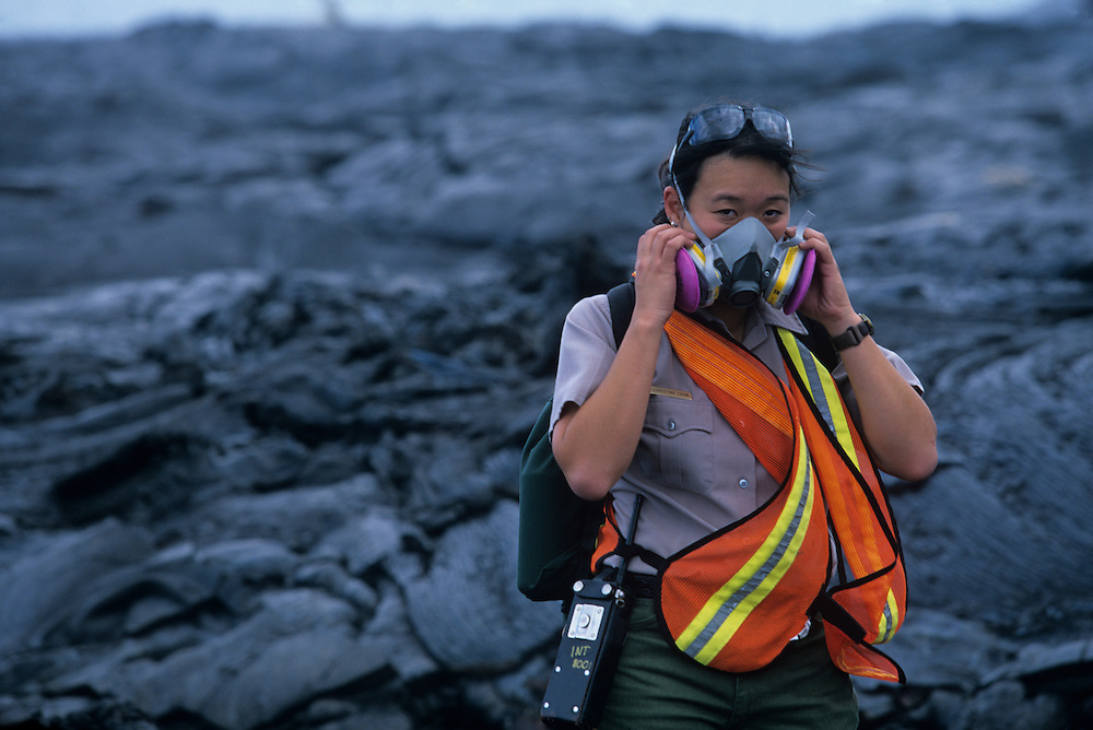 USA, Hawaii, Volcanoes National Park,  Female park ranger wears respirator against fumes from Kilauea volcano eruption
