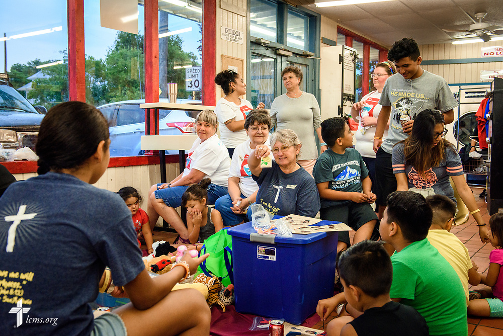 "Volunteers from St. Paul Lutheran Church, San Antonio, Texas, direct games with children at Laundry Love on Wednesday, Aug. 2, 2017, at the E-Z Wash laundromat in San Antonio. The monthly ministry event is supported by a grant through the ""Stand With Your Community"" program, which was made possible by a partnership between the LCMS, Thrivent Financial and Lutheran Church Extension Fund. LCMS Communications/Erik M. Lunsford"