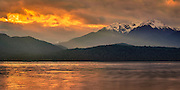 A fiery sunset breaks through a patch of stormy clouds over Lake Te Anau, Fiordland, New Zealand.