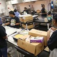 Lauren Wood   Buy at photos.djournal.com<br /> Food service staff members move about the kitchen completing their assigned tasks during the food prep time Friday morning in the cafeteria at Tupelo High School. A staff of 15 people prepares food to serve more than 850 students at the high school daily.