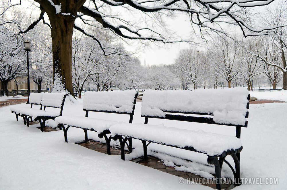Park benches in Lafayette Park opposite the White House in Washington DC covered in a thick layer of snow from a recent snowstorm.