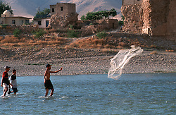 TURKEY HASANKEYF JUL02 - Yound Kurdish boys throw their net in the Tigris river. Since the programme of barrages has commenced on the Tigris, their daily yield has been reduced to a few fish...jre/Photo by Jiri Rezac..© Jiri Rezac 2002..Contact: +44 (0) 7050 110 417.Mobile:  +44 (0) 7801 337 683.Office:  +44 (0) 20 8968 9635..Email:   jiri@jirirezac.com.Web:     www.jirirezac.com