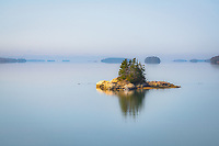 Morning light graces the islands studding the calm and reflective surface of Middle Bay in Brunswick.
