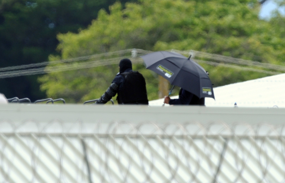 AOS police shade under an umbrella as they keep a watchful eye on two prisoners on another roof at Manawatu Prison, Palmerston North, Thursday, December 13, 2012. Credit:SNPA / Ross Setford