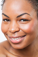 Extreme close-up of smiling young African American woman over white background