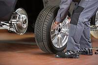 Low section of repairman fixing car's tire in repair shop