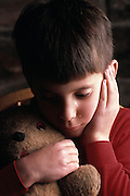 Unhappy boy holding teddy bear crying