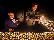 17 MARCH 2017 - KATHMANDU, NEPAL:  People light butter lamps at a Tibetan Buddhist monastery next to Boudhanath Stupa in Kathmandu. Boudhanath Stupa is the holiest site in Nepali Buddhism. It is also the center of the Tibetan exile community in Kathmandu. The Stupa was badly damaged in the 2015 earthquake but was one of the first buildings renovated.      PHOTO BY JACK KURTZ