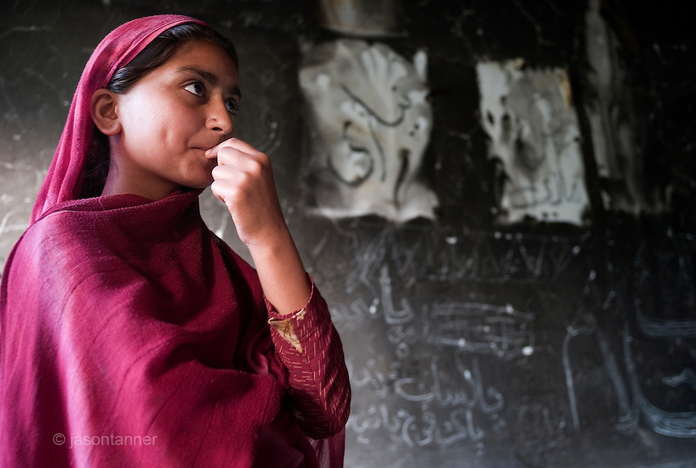 Rabihat, 12 years reflects on he graffiti scribbled on the burnt walls of her classroom.  Her school that was first burnt and then bombed by the taliban shortly after the singing of the peace accord on 18th February 2009 in  Nazarabad near Matta, SWAT. ..Rabihat looks forward to returning to school but as yet funding for new premises and books, resources etc has not materialised from central government..