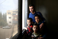 Syrian refugee Bassam Al Rahal, 30, with his sons (left to right) Omar (9), Ammar (5) and Baker (10). The family, which also includes Bassam's wife and daughter, live in an apartment in Tripoli, Lebanon, after fleeing their home in Homs, Syria.