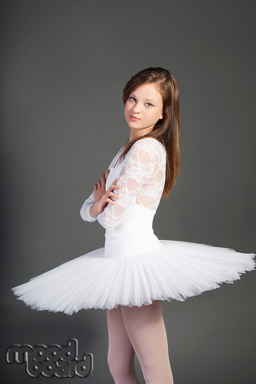 Portrait of young female ballet dancer with arms crossed standing over grey background