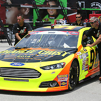 Crew members push the Charlie Crist For Florida Ford paint scheme car driven by Josh Wise down the garage area pavement at Daytona International Speedway on Thursday, July 3, 2014 in Daytona Beach, Florida. Crist, the former Governor of Florida, will run for election again this year.  (AP Photo/Alex Menendez)