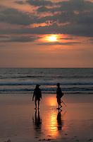 Two fishermen at sunset at Seminyak Beach in Bali, Indonesia