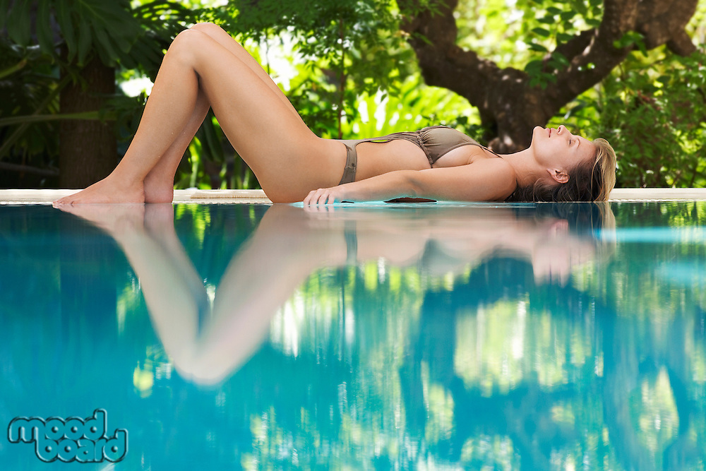Young woman lying by swimming pool portrait profile