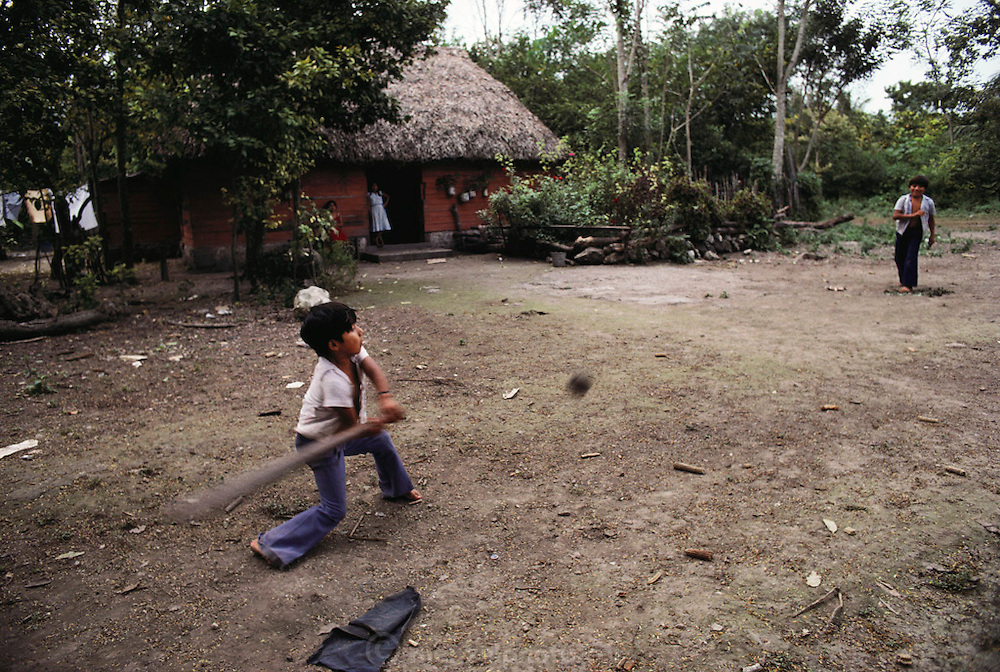 Boys playing baseball in front of their thatched roof house in a Mayan village in the Yucatan, Mexico.
