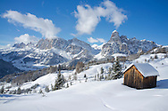 Mounts Lavarella, Conturines and Sasongher behind a snow covered wooden barn at the Alta Badia ski resort near Corvaro, The Dolomites, South Tyrol, Italy