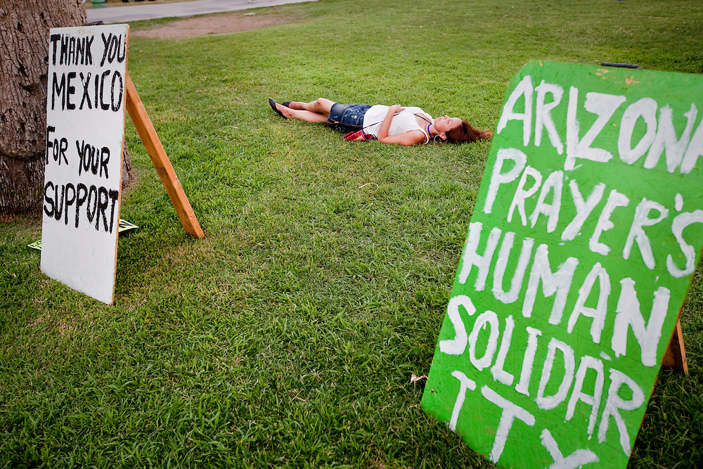A protester is seen laying on the grass of Arizona's State Capitol.
