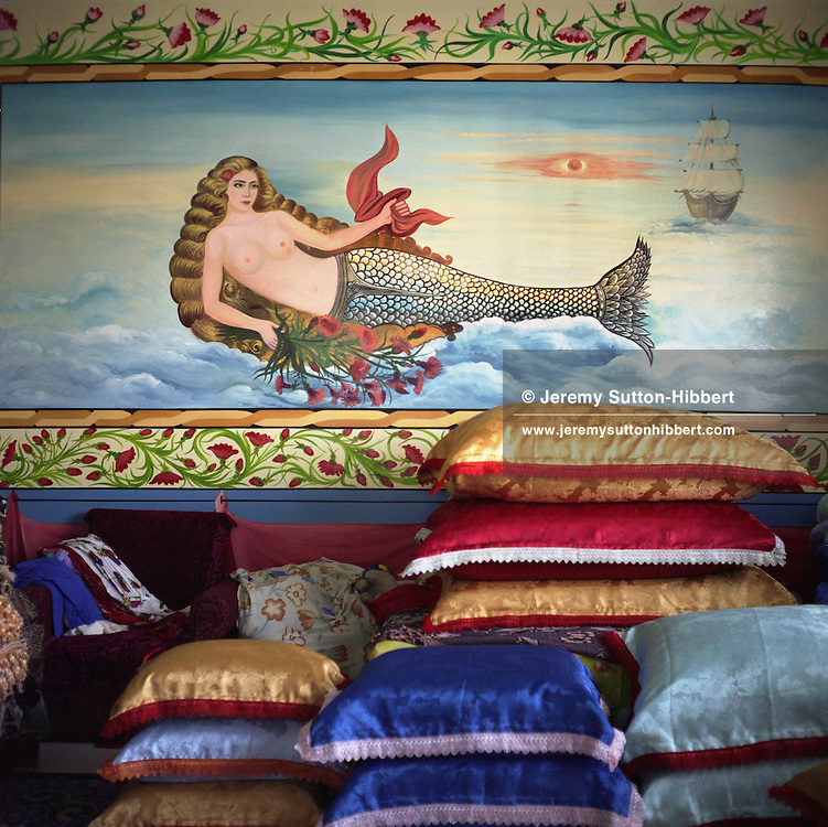 A mermaid painted on the wall of a Roma home, in the new part of the Sintesti Roma camp. Mermaids are very popular as wall decoration, but no-one within the camp knows the reason why they were first painted. The cushions are a wedding present for a forthcoming wedding, of Nadia, aged 14..