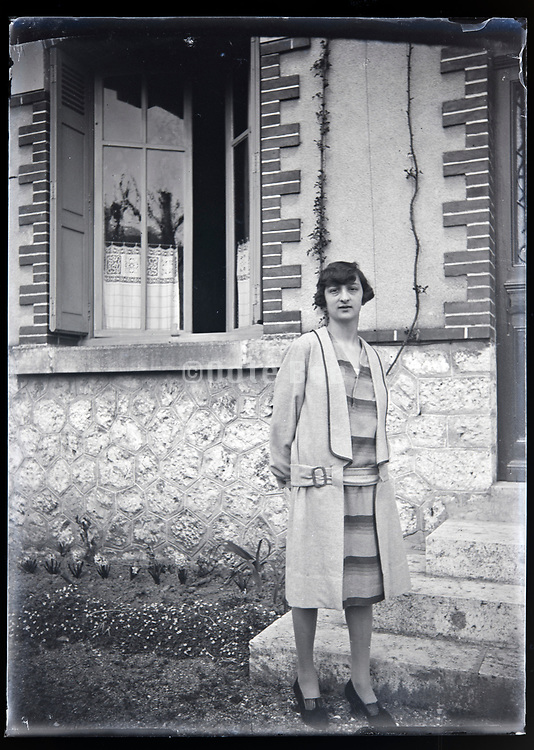 woman posing in front of a house France circa 1920s