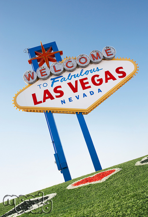 Welcome to Las Vegas sign with playing card suits in grass