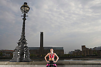 Triathlon athlete wearing gold medal standing against river embankment London England