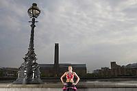Triathlon athlete wearing gold medal standing against river embankment London England