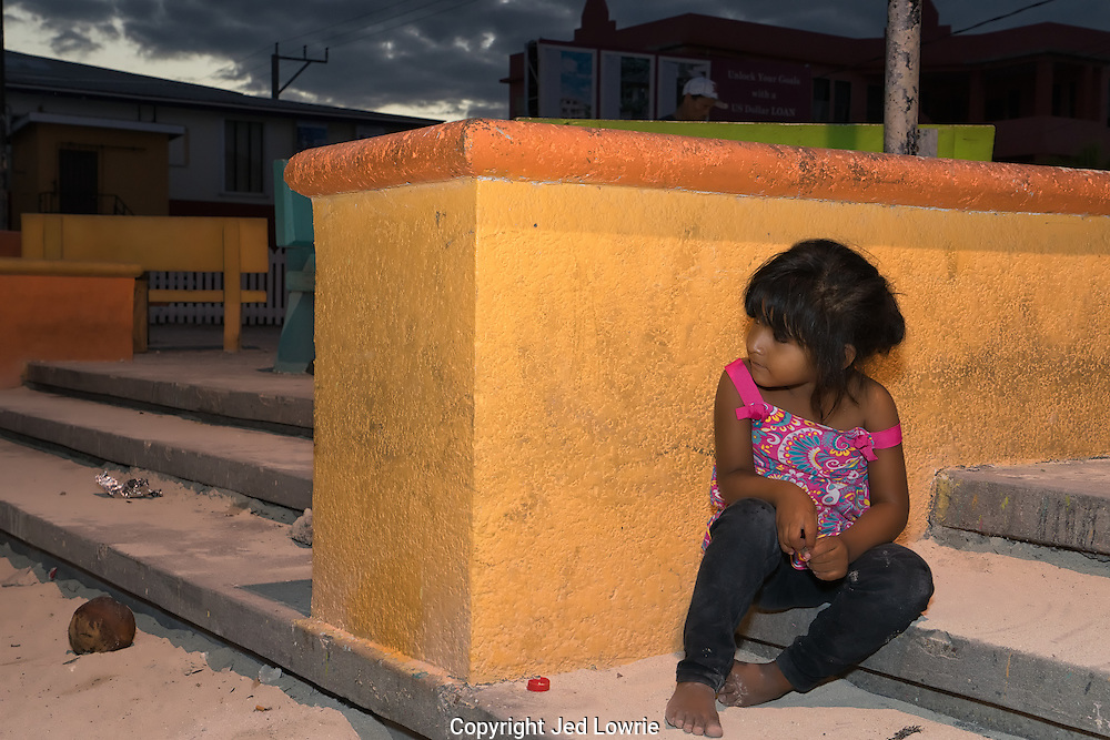 A beautiful little girl in a small town in Belize peers around the corner to watch some young boys play soccer. The colors and mood of this photo are striking.