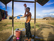 06 NOVEMBER 2014 - SITTWE, RAKHINE, MYANMAR: A Rohingya man bathes in an IDP camp for Rohingya Muslims near Sittwe. After sectarian violence devastated Rohingya communities and left hundreds of Rohingya dead in 2012, the government of Myanmar forced more than 140,000 Rohingya Muslims who used to live in and around Sittwe, Myanmar, into squalid Internal Displaced Persons camps. The government says the Rohingya are not Burmese citizens, that they are illegal immigrants from Bangladesh. The Bangladesh government says the Rohingya are Burmese and the Rohingya insist that they have lived in Burma for generations. The camps are about 20 minutes from Sittwe but the Rohingya who live in the camps are not allowed to leave without government permission. They are not allowed to work outside the camps, they are not allowed to go to Sittwe to use the hospital, go to school or do business. The camps have no electricity. Water is delivered through community wells. There are small schools funded by NOGs in the camps and a few private clinics but medical care is costly and not reliable.   PHOTO BY JACK KURTZ