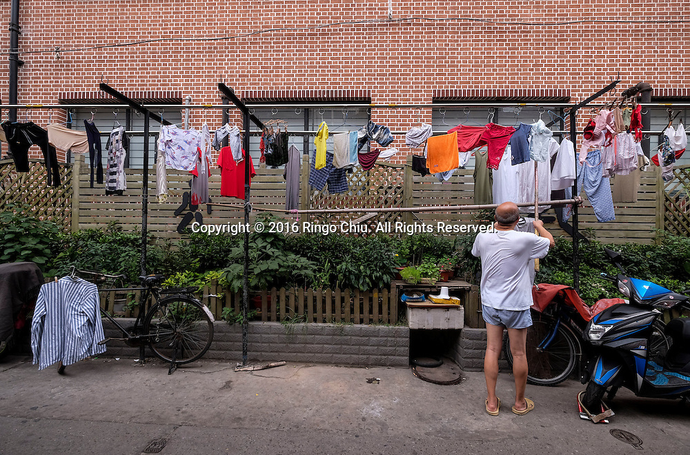 A man hangs clothes to dry in an old alley off of the Nanjing Road Pedestrian Street in Shanghai, China. Shanghai is the most populous city in China and the most populous city proper in the world. It is one of the four direct-controlled municipalities of China, with a population of more than 24 million as of 2014. It is a global financial centre, and a transport hub with the world's busiest container port. Located in the Yangtze River Delta in East China, Shanghai sits on the south edge of the mouth of the Yangtze in the middle portion of the Chinese coast. The municipality borders the provinces of Jiangsu and Zhejiang to the north, south and west, and is bounded to the east by the East China Sea. A major administrative, shipping, and trading town, Shanghai grew in importance in the 19th century due to trade and recognition of its favourable port location and economic potential. The city was one of five forced open to foreign trade following the British victory over China in the First Opium War while the subsequent 1842 Treaty of Nanking and 1844 Treaty of Whampoa allowed the establishment of the Shanghai International Settlement and the French Concession. The city then flourished as a center of commerce between China and other parts of the world (predominantly Western countries), and became the primary financial hub of the Asia-Pacific region in the 1930s. However, with the Communist Party takeover of the mainland in 1949, trade was limited to socialist countries, and the city's global influence declined. In the 1990s, the economic reforms introduced by Deng Xiaoping resulted in an intense re-development of the city, aiding the return of finance and foreign investment to the city. Shanghai has been described as the &quot;showpiece&quot; of the booming economy of mainland China; renowned for its Lujiazui skyline, museums and historic buildings, such as those along The Bund, the City God Temple and the Yu Garden.(Photo by Ringo Chiu/PHOTOFORMULA.com)<br /> <br /> Usa