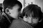 A boy whispers in hiw friend's ear.