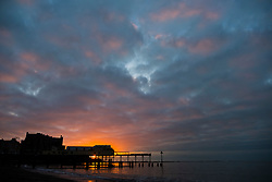 © Licensed to London News Pictures. 03/01/2018. Aberystwyth, UK. 03/01/2019. At the end of a grey dull and cold January day the sun makes a brief appearance as it sets over the Royal Pier in Aberystwyth on the Cardigan Bay coast of west Wales. Photo credit: Keith Morris/LNP