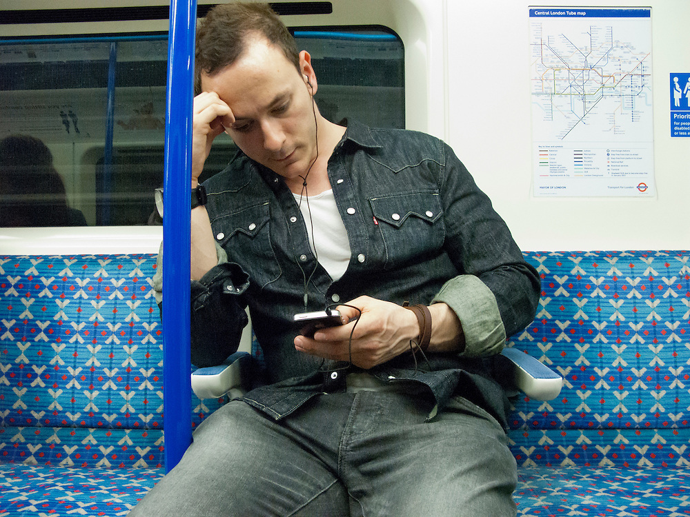 Portrait of a man listening to music and reading on a personal electronic device